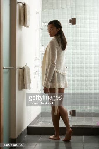 Young Woman Opening Glass Door Into Shower Stall Rear View