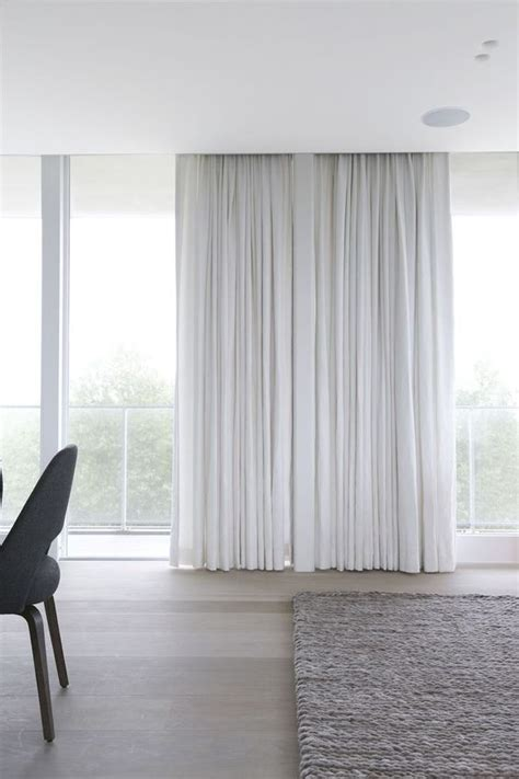 Floor to ceiling white drapes and oatmeal woven carpet for